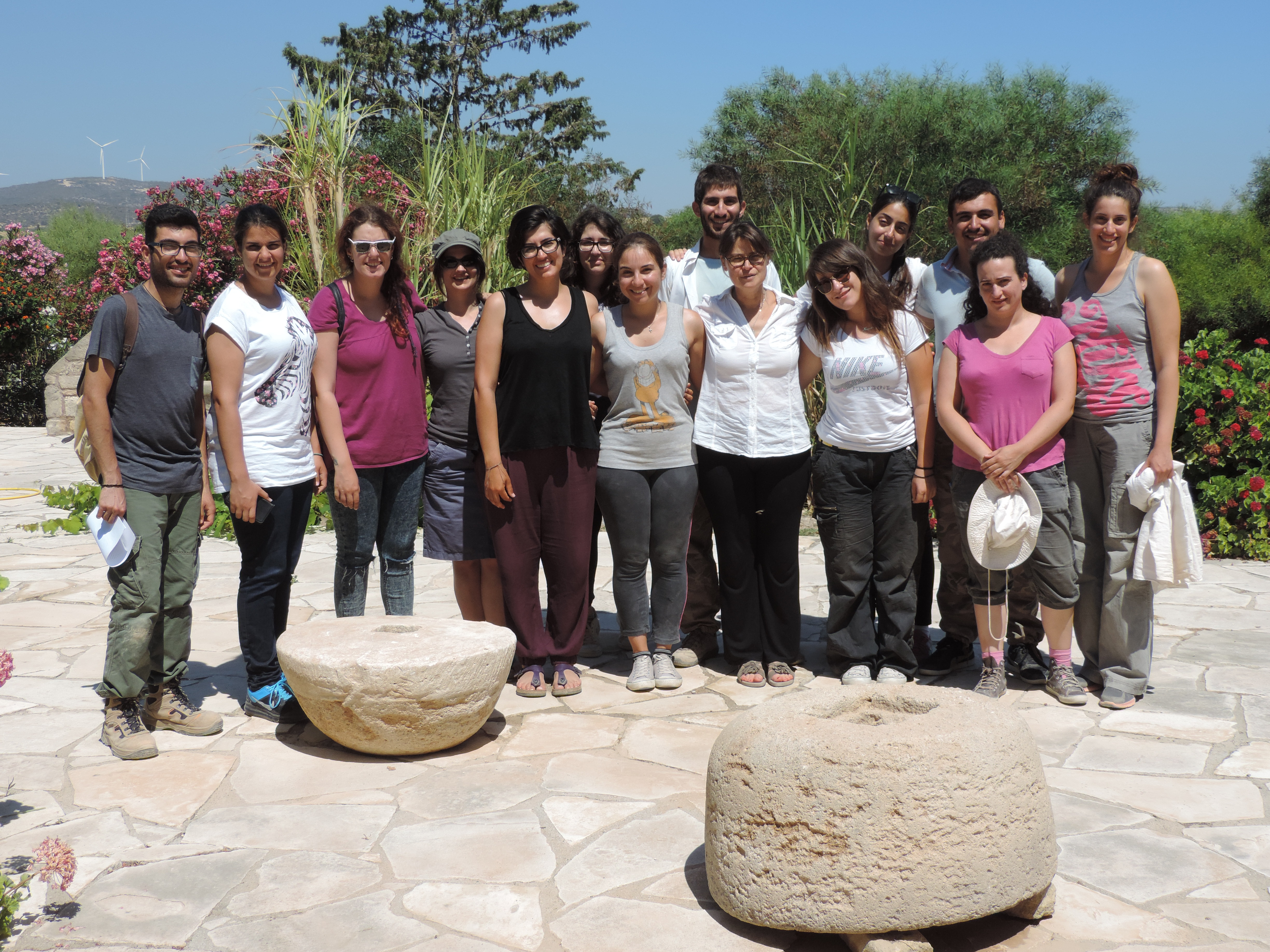Fig. 11 - The 2015 excavation team with the two millstones now at the Kouklia Museum